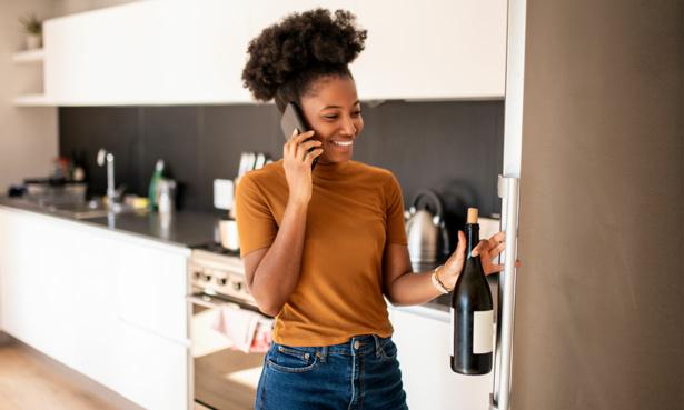woman taking bottle of wine from fridge