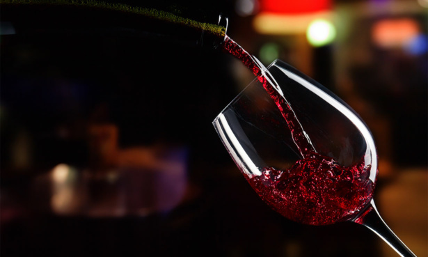 Pouring glass of wine at night