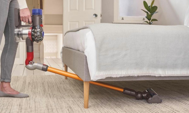 Someone using Dyson's Reach Under tool to clean under their sofa