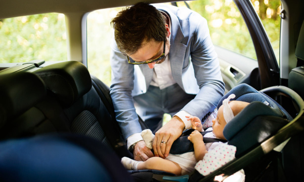 Father fitting baby into car seat in car