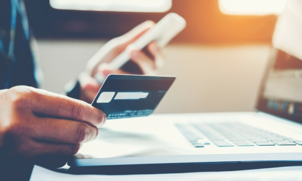 someone paying off a credit card using a laptop and a mobile phone