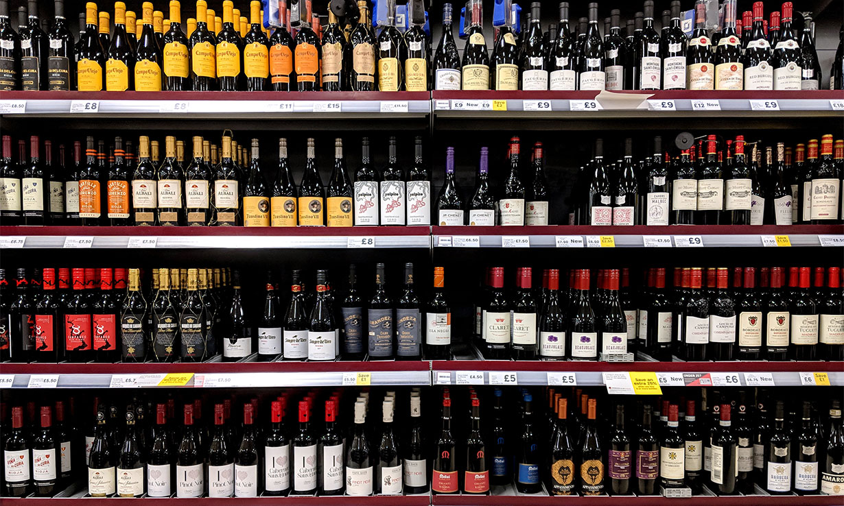 Supermarket shelves stocked with bottles of red wine