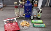 Craft Gin Club - blue bottle of gin, double dutch mixers, two bars of Tony's chocolonely bars, dried orange slices, Tyrell's sweet chilli & red pepper crisps, jam