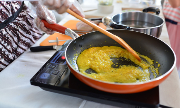 Person cooking curry in a pan