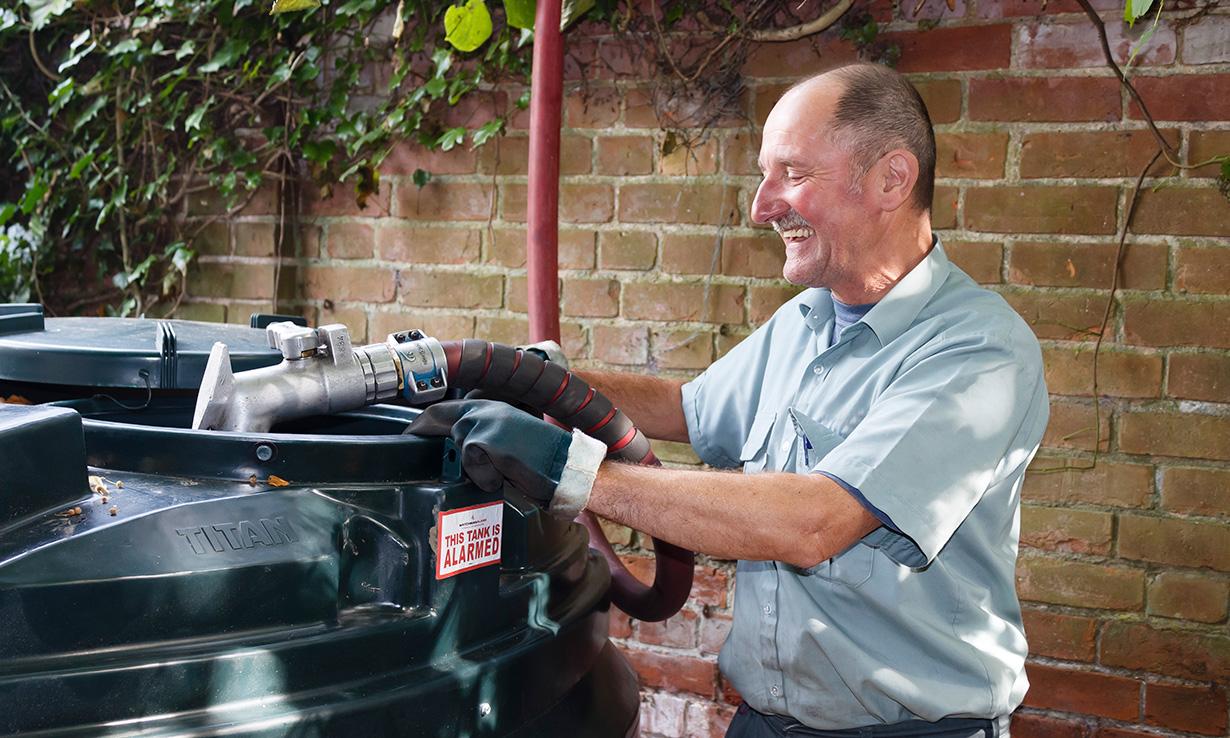 man filling a heating oil tank with kerosene