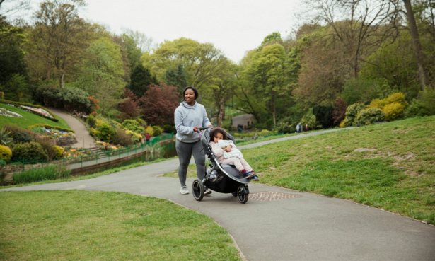 Person pushing buggy through a park