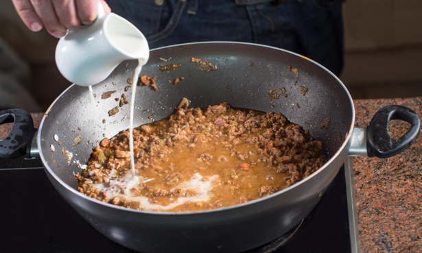 Pouring milk into bolognese sauce