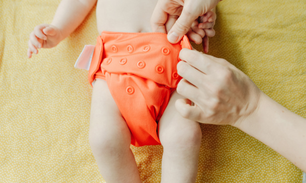 Baby wearing an orange reusable nappy