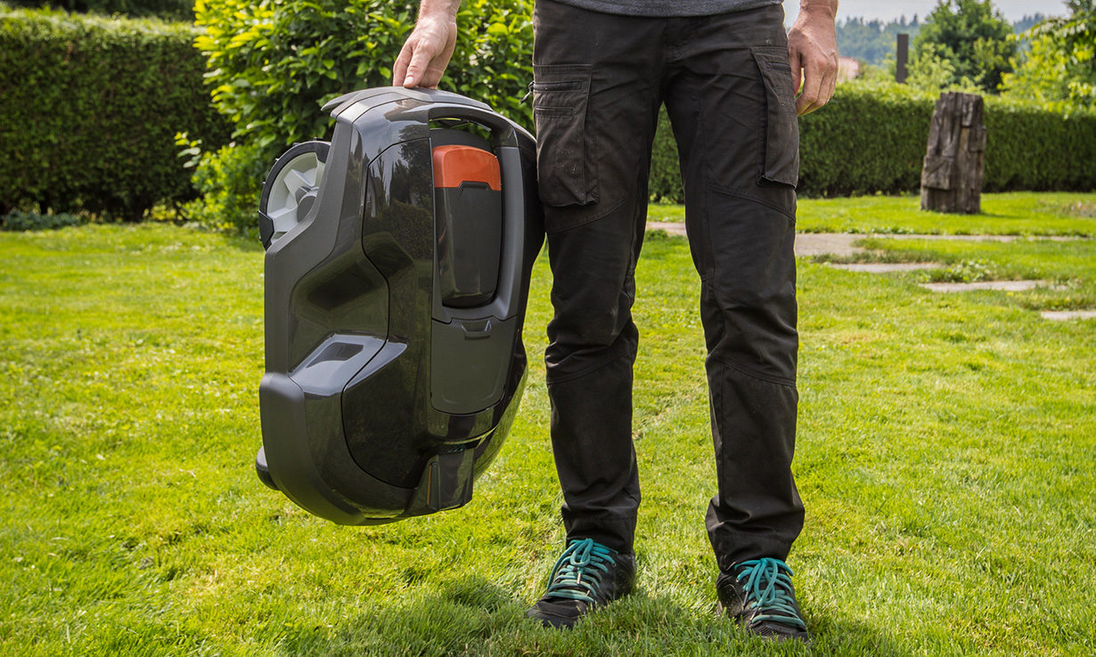 Someone carrying a robot lawn mower in a garden