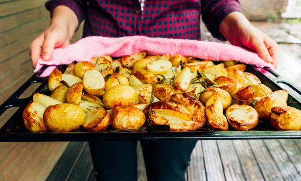 Person holding a tray of roast potatoes