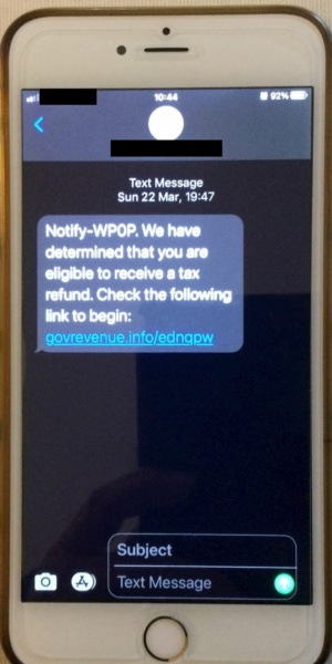 Picture of a phone screen with the scam HMRC text message