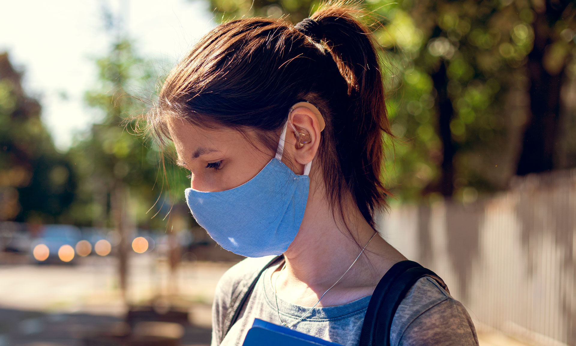 A woman wearing a face mask and a hearing aid