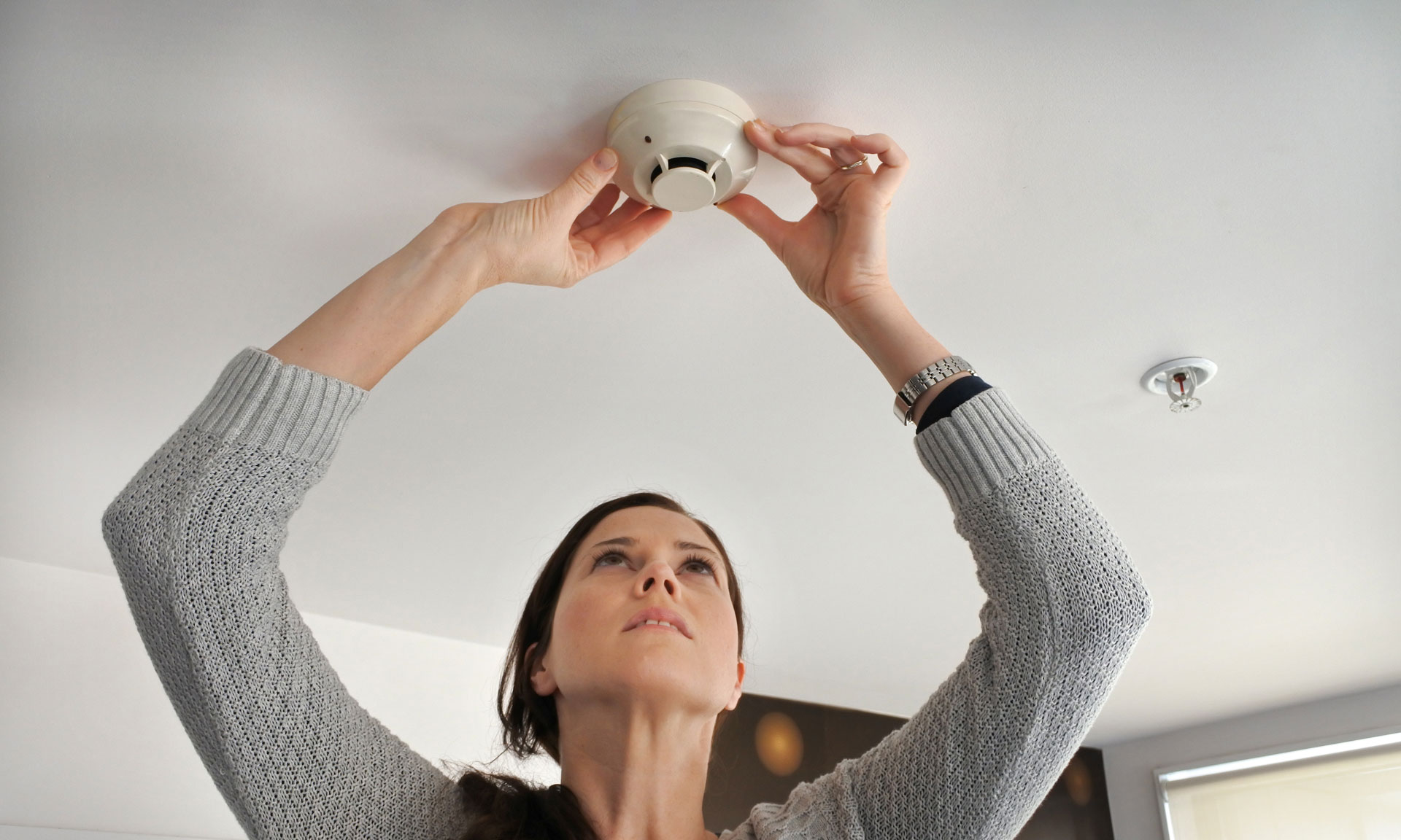 Woman fitting a smoke alarm to the ceiling.