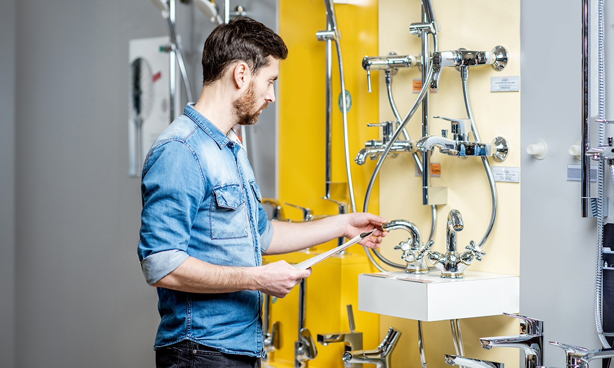 Man in bathroom showroom looking at taps and showers