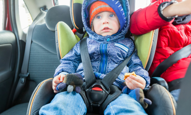 badly strapped in child in car seat