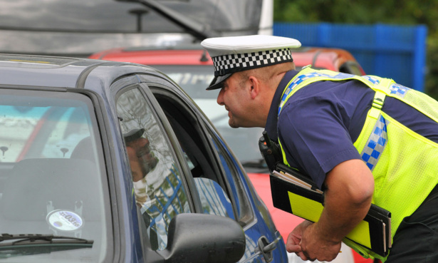 policeman checking inside car for car seat