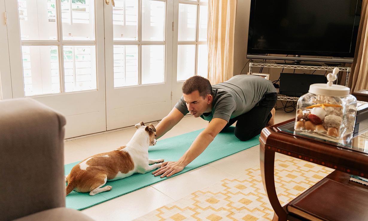 Man doing yoga with his dog