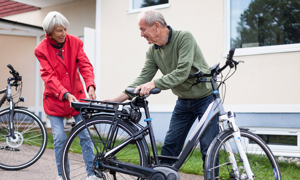 Older couple putting battery on electric bike