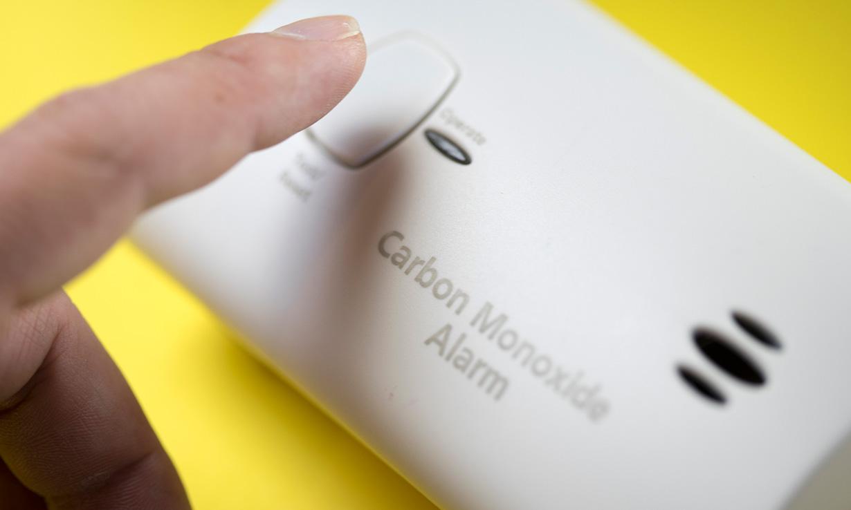 Person testing carbon monoxide alarm by pressing test button