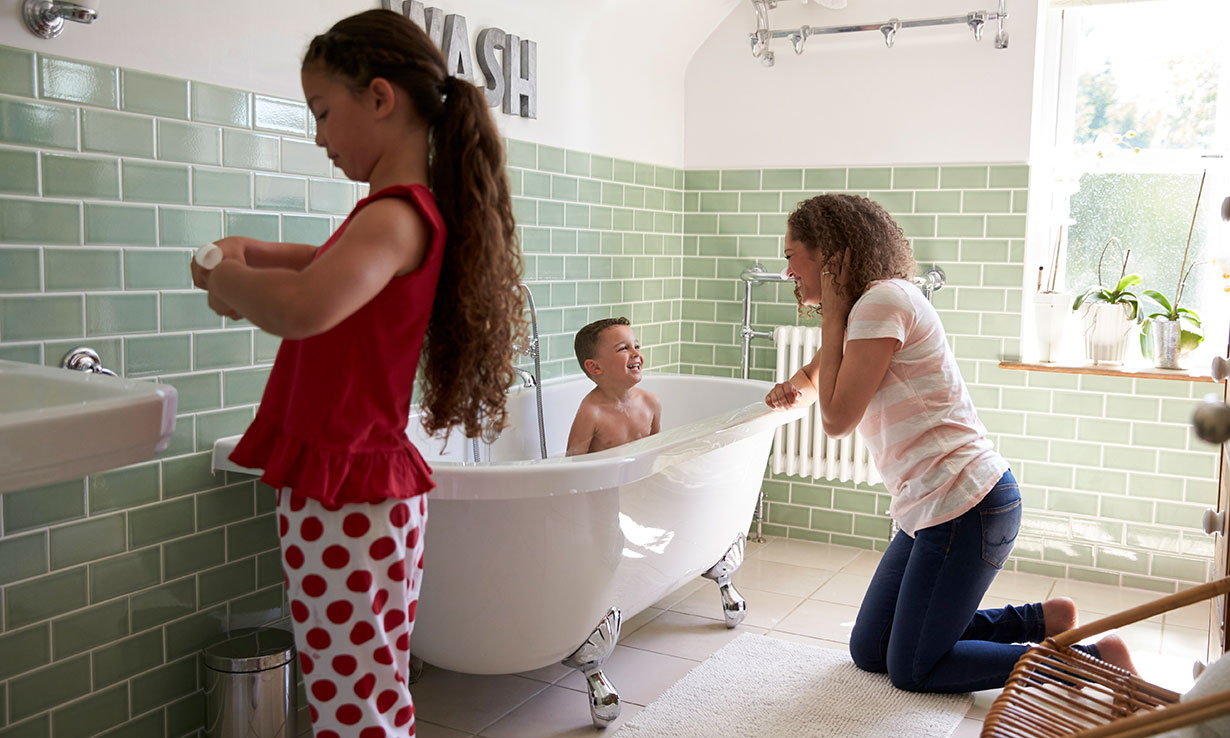 Girl brushing her teeth at the sink while a boy is in the bath and woman supervises