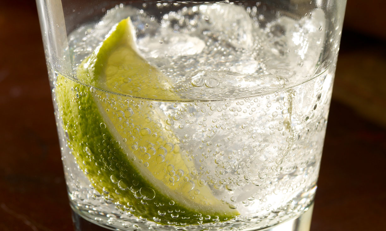 A close up of a gin and tonic with ice and lime