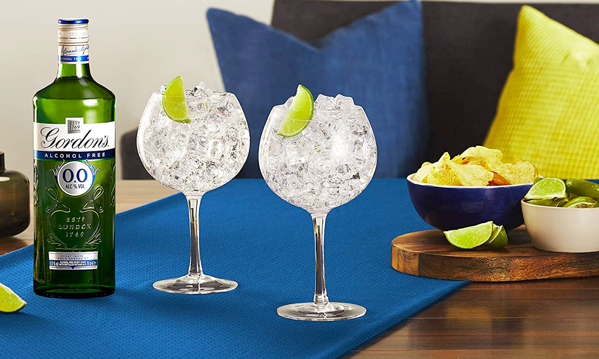 Gordon's 0.0% Alcohol Free Gin next to two gin and tonics and a bowl of crisps