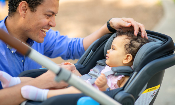 Parent looking at baby sitting in car seat attached to pushchair