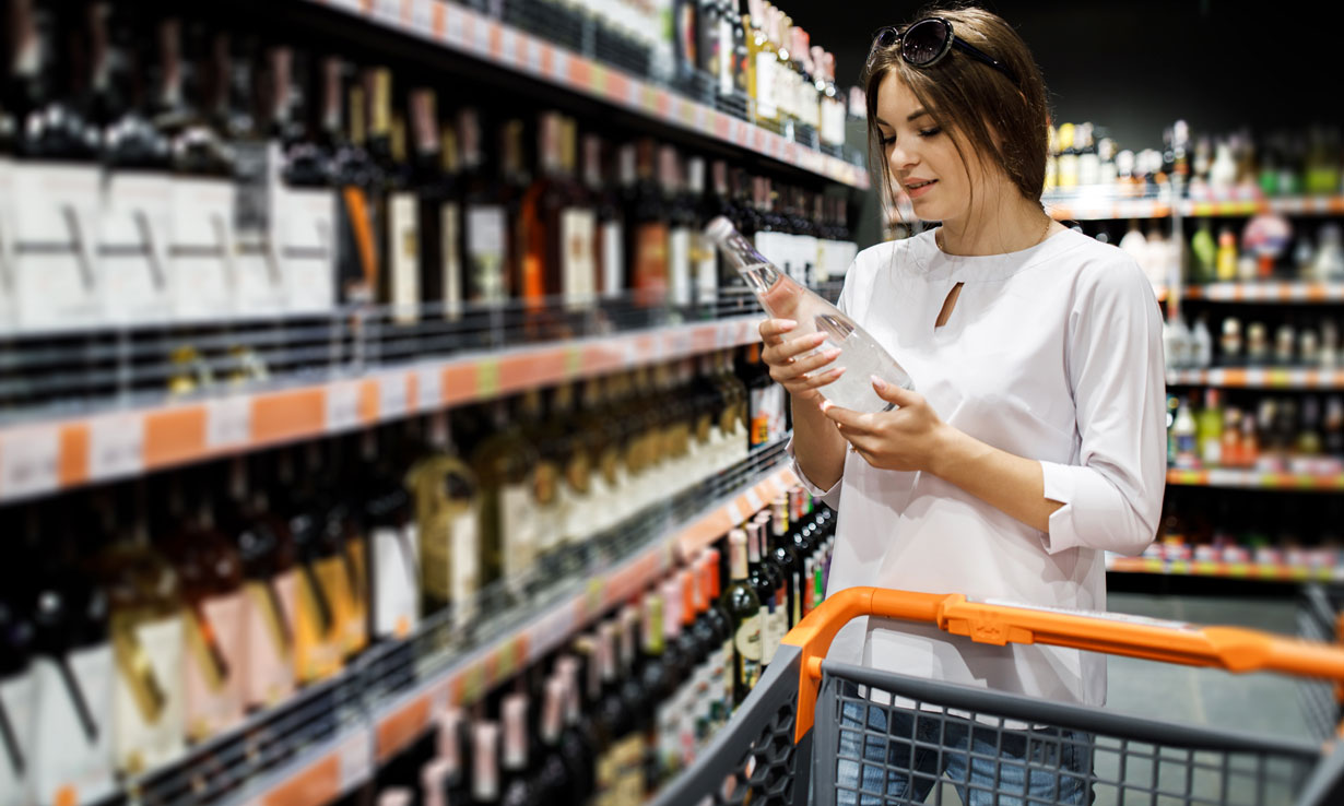 A woman shopping for alcohol at the supermarket