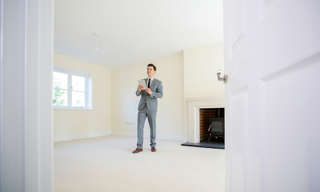 estate agent in an empty living room doing a home valuation