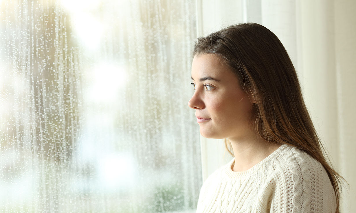 Woman staring through a rain soaked window