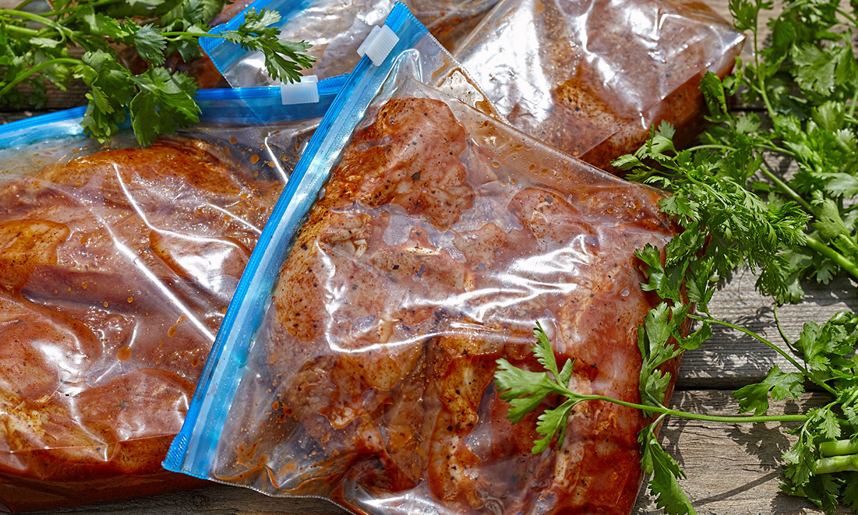 Chicken marinating in sealed bags