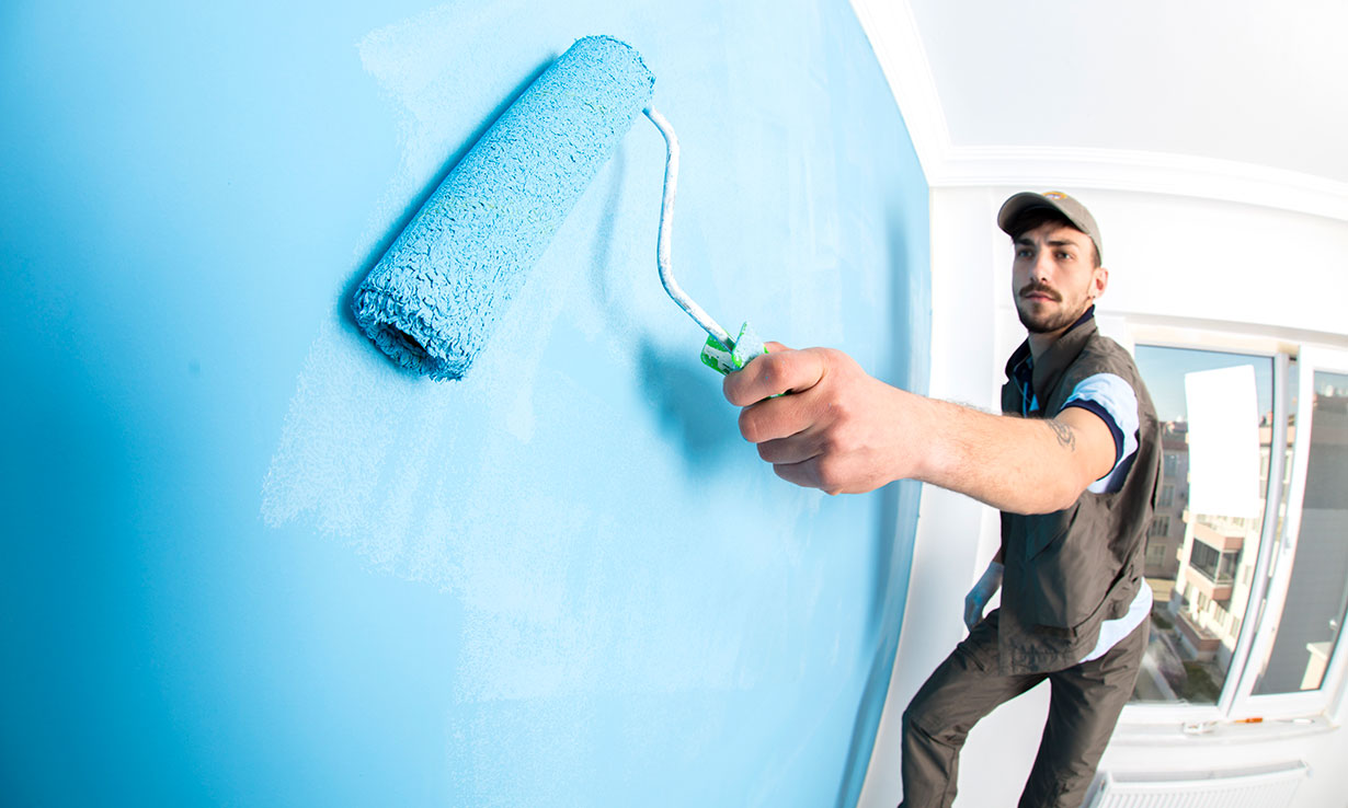 Man painting a wall blue with a roller