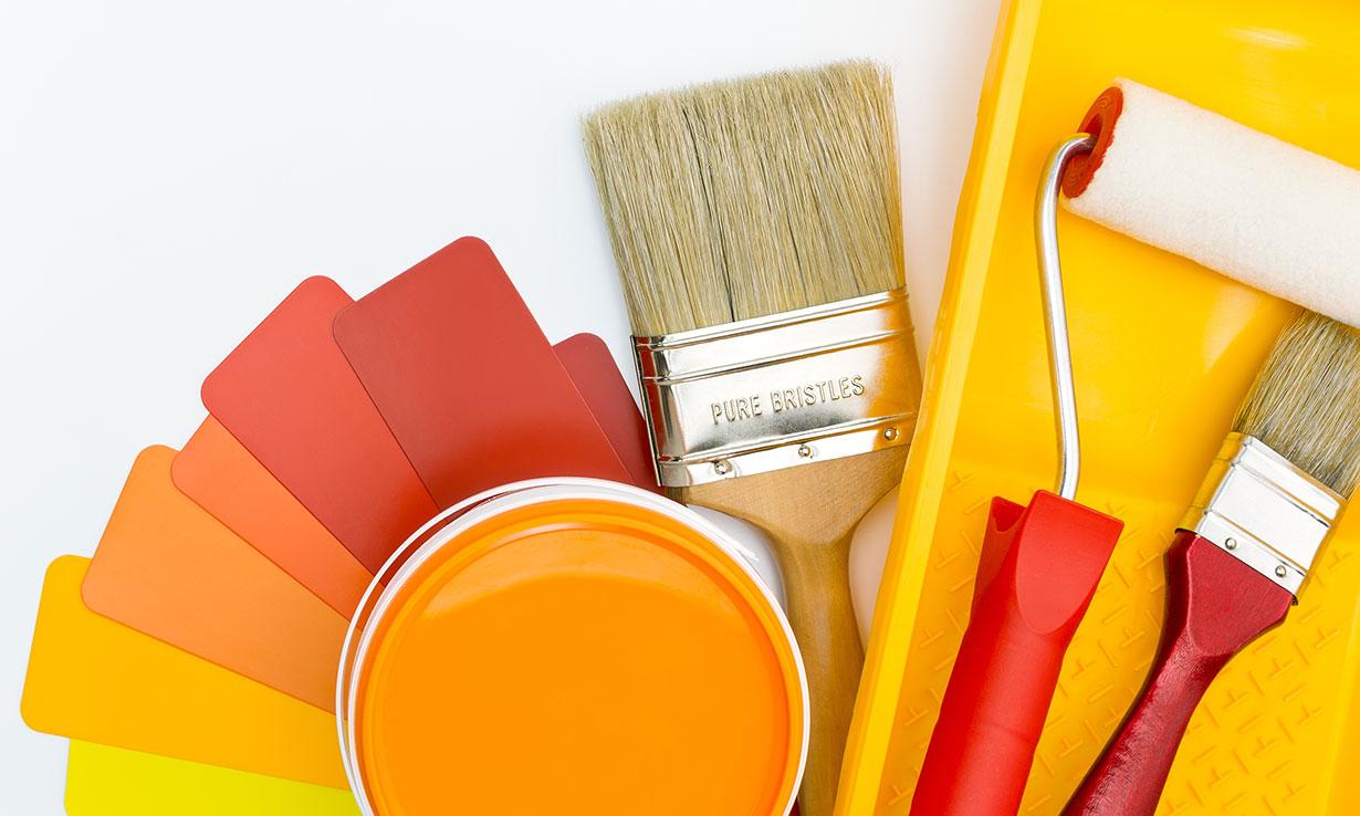 Tin of orange paint, paintbrush and roller