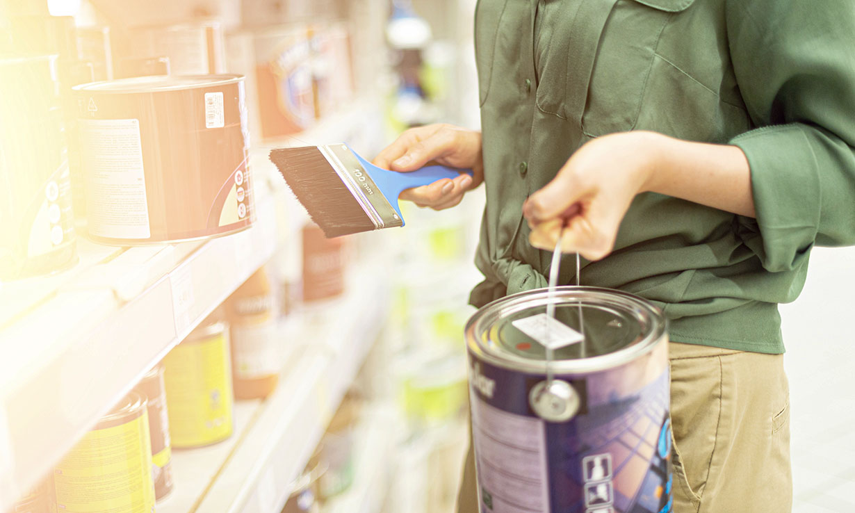 Person shopping for paint in a DIY store