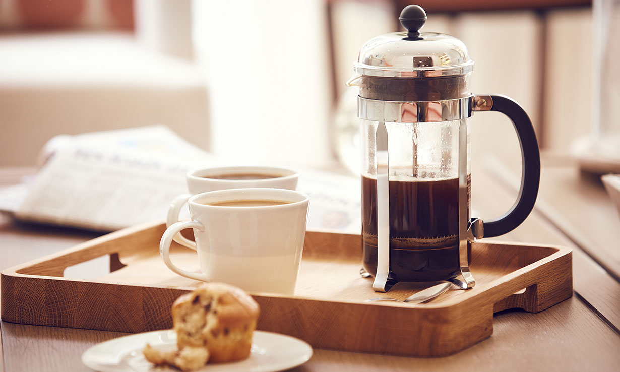 Cafetiere, cups of coffee and a muffin