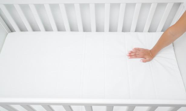 hand testing firmness of cot mattress