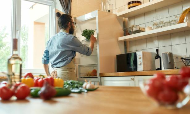 Man putting food in the fridge