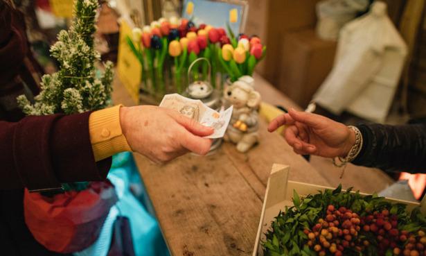 hands exchanging cash in flower shop