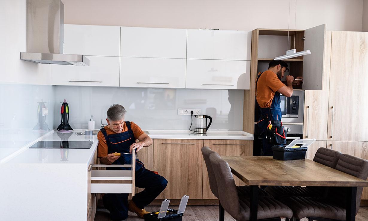 Two men fitting white kitchen units